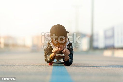 istock Young Boy Imagines Flying On Skateboard 635697962