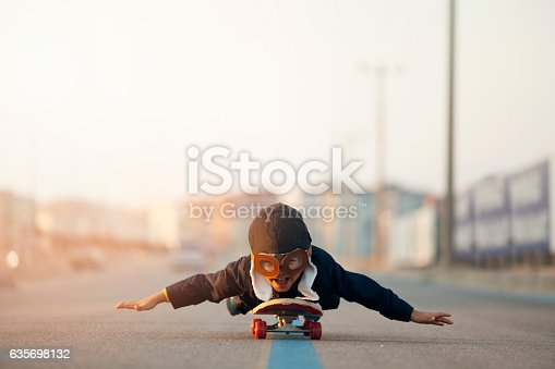 istock Young Boy Imagines Flying On Skateboard 635698132