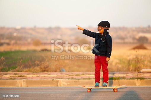 istock Young Boy Imagines with pilot helmet On Skateboard 625794636