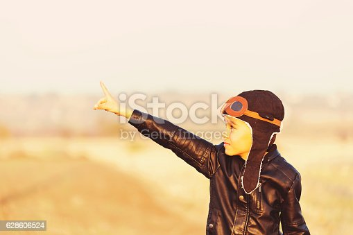istock Young Boy Imagines with pilot helmet On Skateboard 628606524