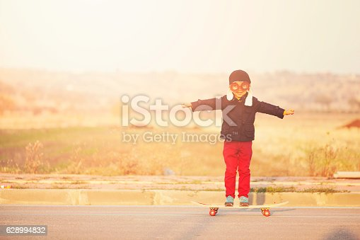 495731108 istock photo Young Boy Imagines with pilot helmet On Skateboard 628994832