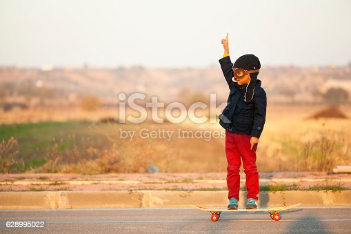 istock Young Boy Imagines with pilot helmet On Skateboard 628995022