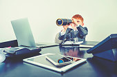 istock Young boy in a business suit with telescope. 1251408959