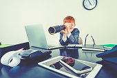 istock Young boy in a business suit with telescope. 1251408965