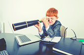 istock Young boy in a business suit with telescope. 1251408970