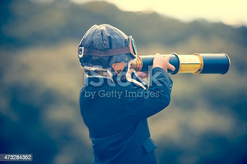 istock Young boy in a business suit with telescope. 473284352