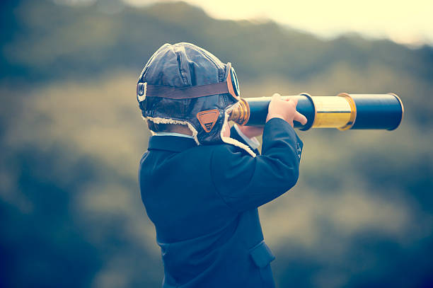 Young boy in a business suit with telescope. Young boy in a business suit with telescope. Small child wearing a full suit and holding a telescope. He is holding the telescope up to his eye with an aviator cap on. Business forecasting, innovation, leadership and planning concept. Shot outdoors with trees and grass in the background the way forward stock pictures, royalty-free photos & images