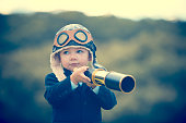 istock Young boy in a business suit with telescope. 473284370