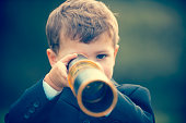 istock Young boy in a business suit with telescope. 473284380