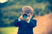 istock Young boy in a business suit with telescope. 473284384