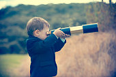 istock Young boy in a business suit with telescope. 473300156