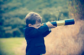 istock Young boy in a business suit with telescope. 494279086