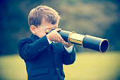 istock Young boy in a business suit with telescope. 494279156
