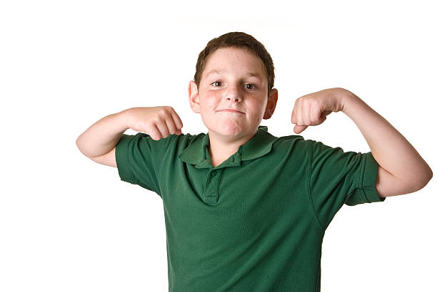 Young boy in a green polo shirt flexing stock photo