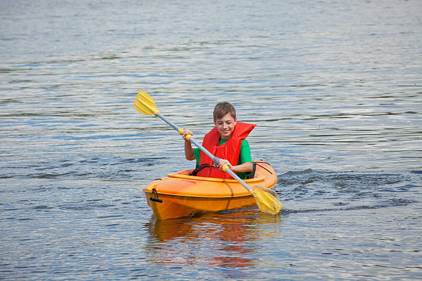 young boy in a kayak - kajak paddel stock-fotos und bilder