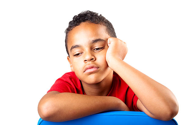A young boy in a red shirt is bored and tired  stock photo