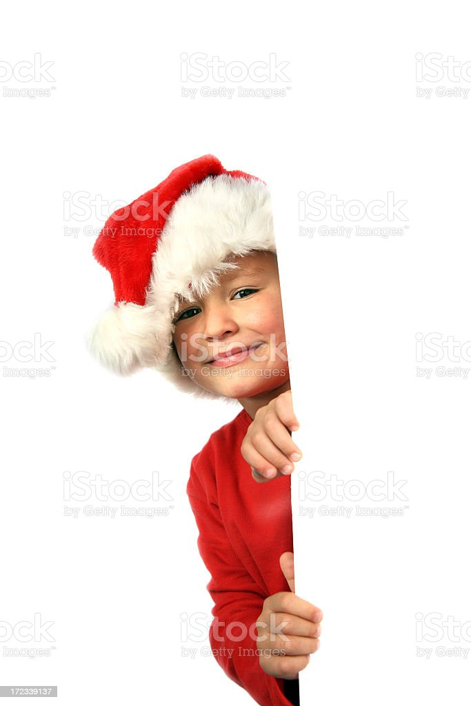 Young boy in a Santa Claus costume peering around a corner royalty-free stock photo