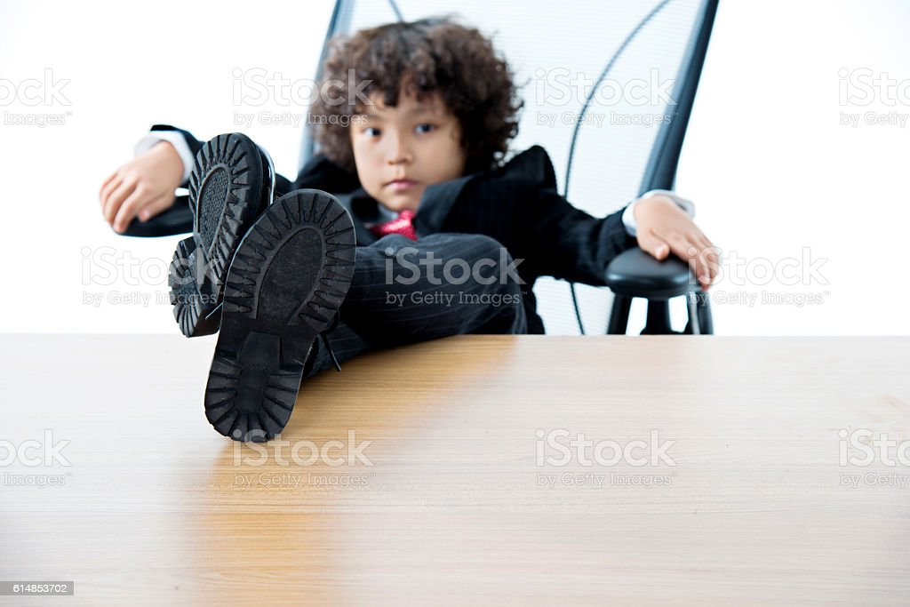 Young boy in a suit with feet up on desk stock photo