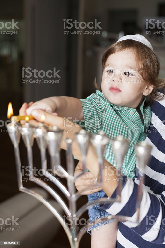 Young boy in adult's arms helping to light a menorah stock photo