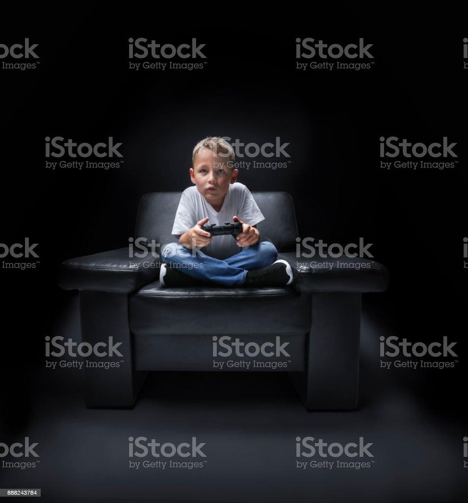 kleiner Junge im Sessel vor dem Fernseher und spielt mit Controller – Foto