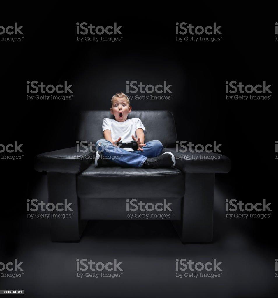 kleiner Junge im Sessel vor dem Fernseher und schreit – Foto