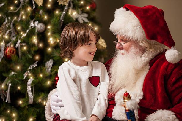 junge in ehrfurcht liegt an santa's runde - santa stock-fotos und bilder