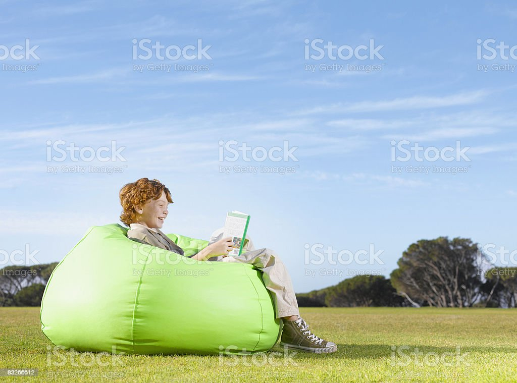 Young boy in bean bag reading outdoors royalty-free stock photo