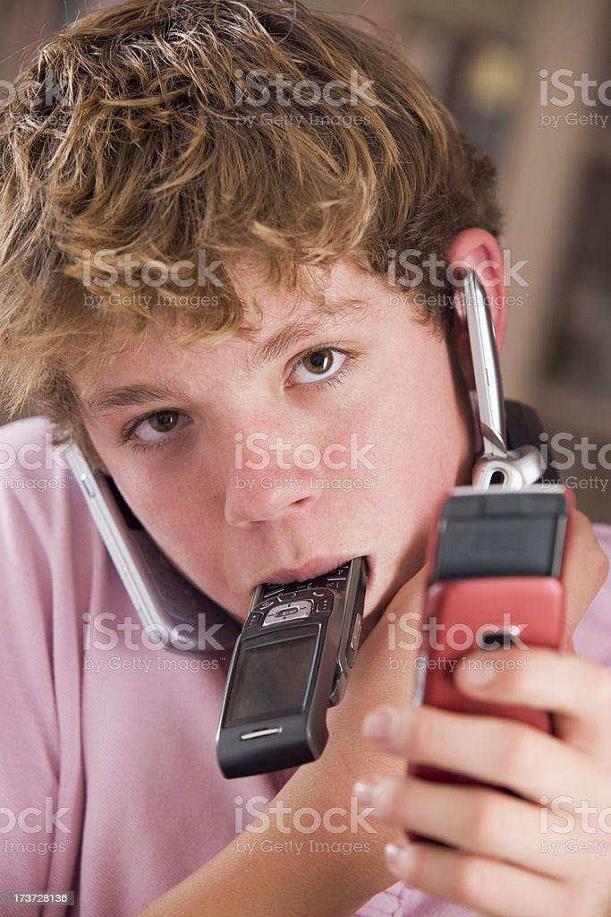 Young boy in bedroom holding many cellular phones royalty-free stock photo