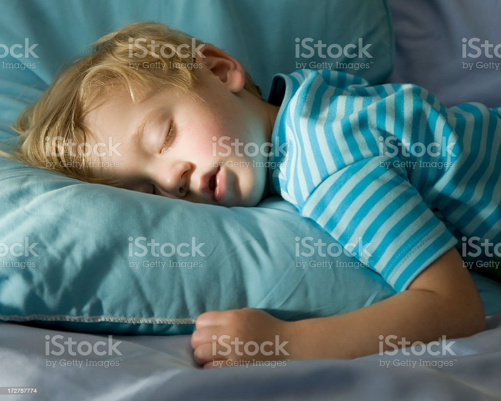 Young boy in blue, peacefully sleeping on a blue pillow stock photo