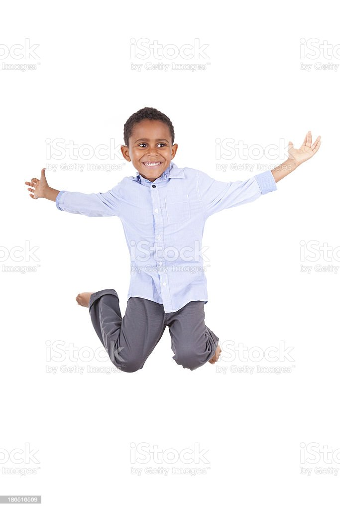 Young boy in blue shirt and slacks jumping in the air royalty-free stock photo