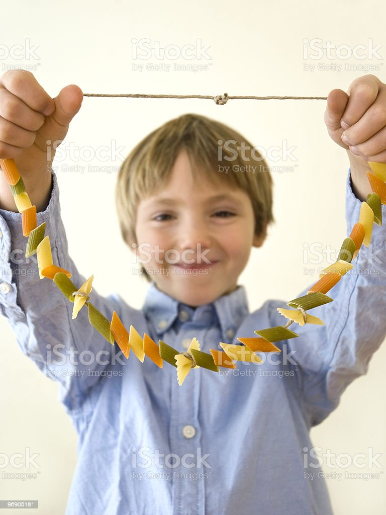 Young boy in blue shirt holding up a pasta necklace royalty-free stock photo