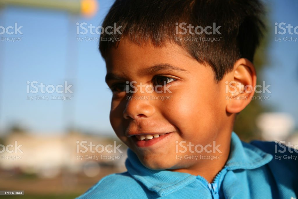 Young boy in blue sweater outside in sunshine stock photo