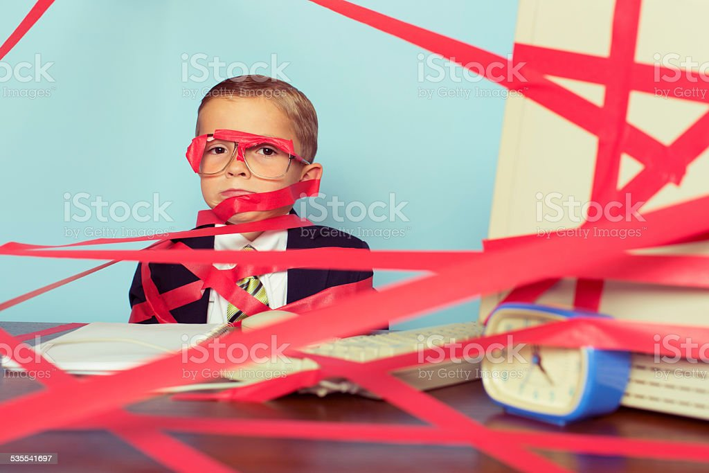 Young Boy in Business Suit Covered in Red Tape stock photo