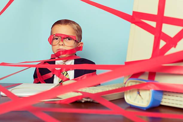 kleiner junge im business-anzug mit roten band - rot bekümmerte möbel stock-fotos und bilder