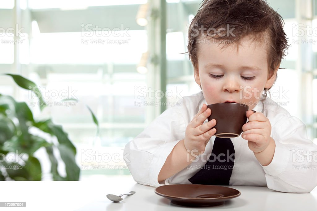 Young boy in business-wear drinking from a brown cup stock photo