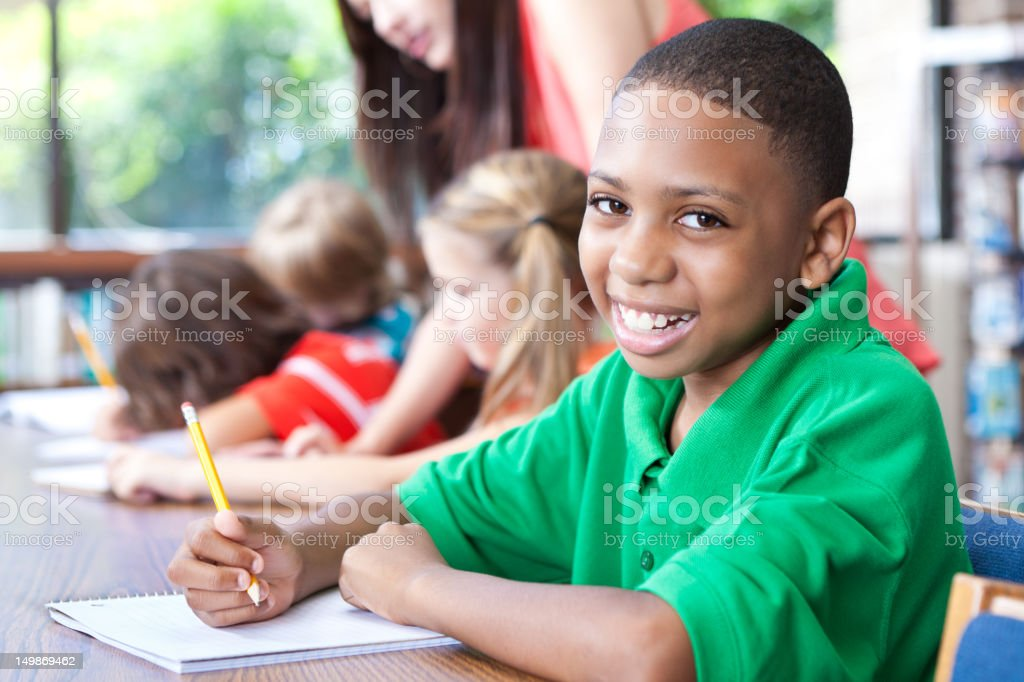 Young boy in class with other students and teacher royalty-free stock photo