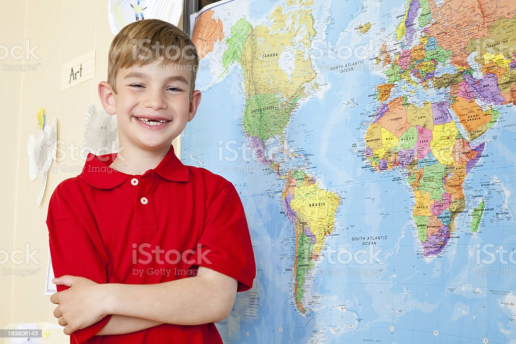 Young Boy In Class With World Map and Art Projects stock photo