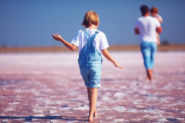 kleiner junge in jeans strampler zu fuß durch den rosa salzsee firth - jeans overall stock-fotos und bilder