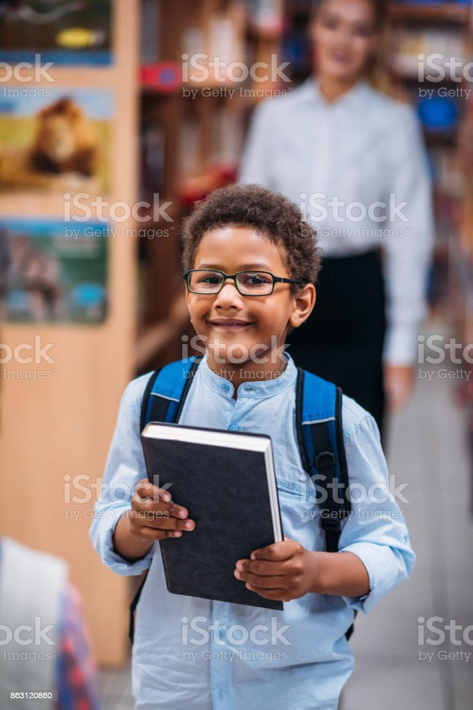 young boy in library with teacher stock photo