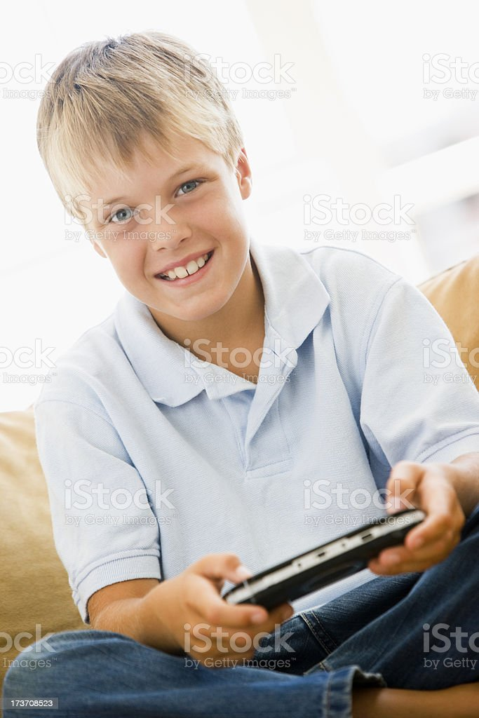 Young boy in living room with handheld video game smiling royalty-free stock photo