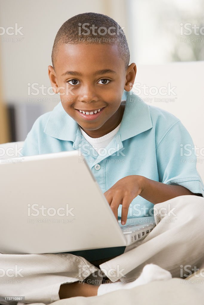 Young boy in living room with laptop smiling royalty-free stock photo