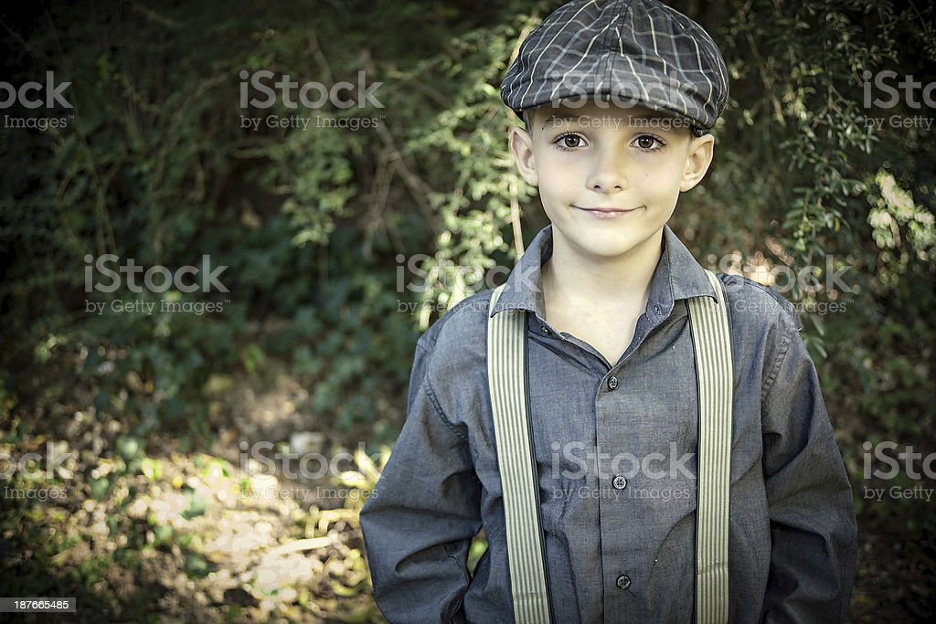 Young Boy in Newsboy Hat and Suspenders Standing Outside stock photo