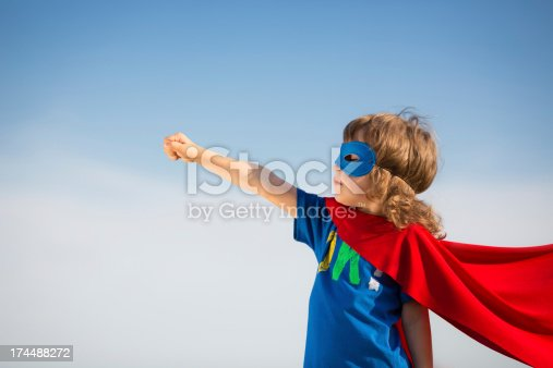 istock Young boy in red superhero cape and mask 174488272