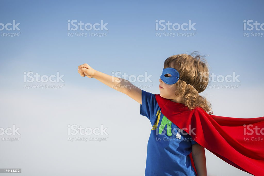 Young boy in red superhero cape and mask stock photo