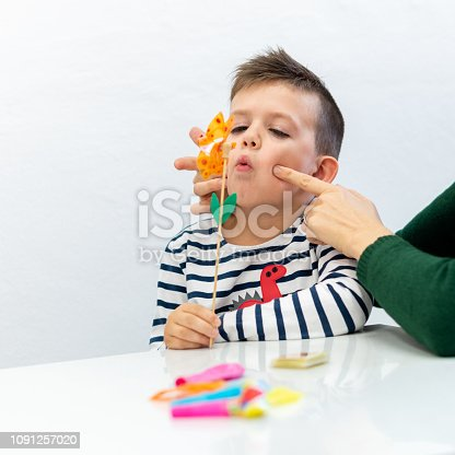 istock Young boy in speech therapy office. Preschooler exercising correct pronunciation with speech therapist. 1091257020