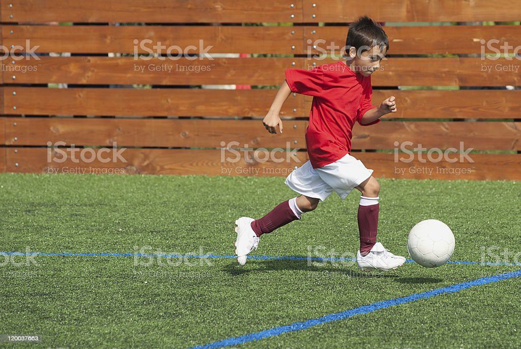 A young boy in sports wear playing soccer royalty-free stock photo