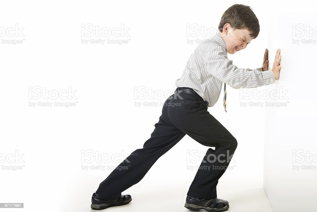 Young boy in suit pushing against wall stock photo