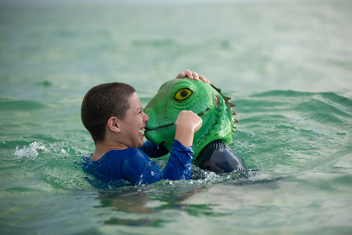 Young boy in the beach fighting with his father that wears a lizard mask