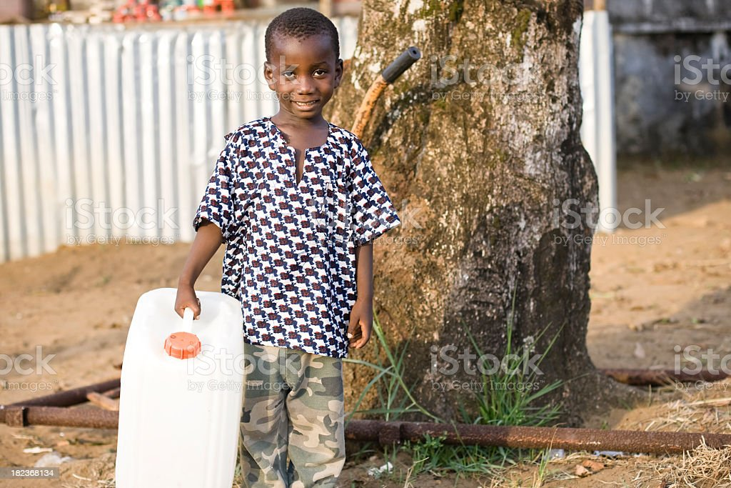 Young boy in third world country holding water jug stock photo