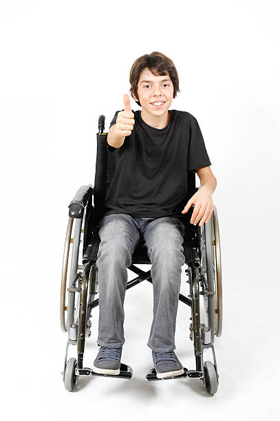 Young Boy in wheelchair giving thumb's up stock photo